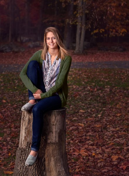 senior girl sitting on a tree